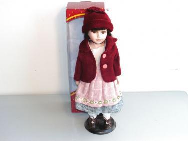 Porcelánová panenka v červeném kabátku